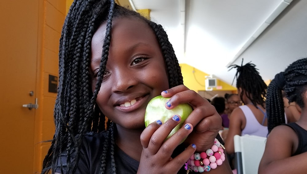 A summer camper enjoys an apple provided by Fresh Food Factor
